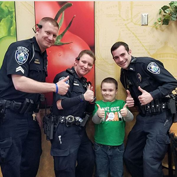 Three police officers standing with a little boy all giving the thumbs up