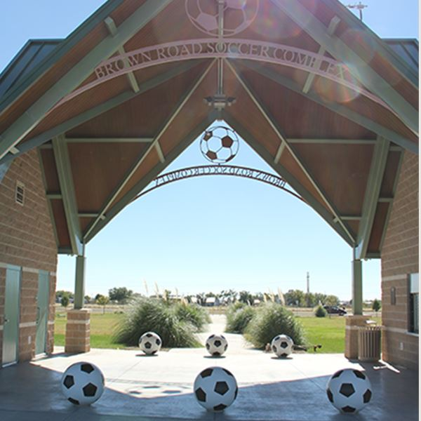Enlarged soccer balls under a green roof entrance