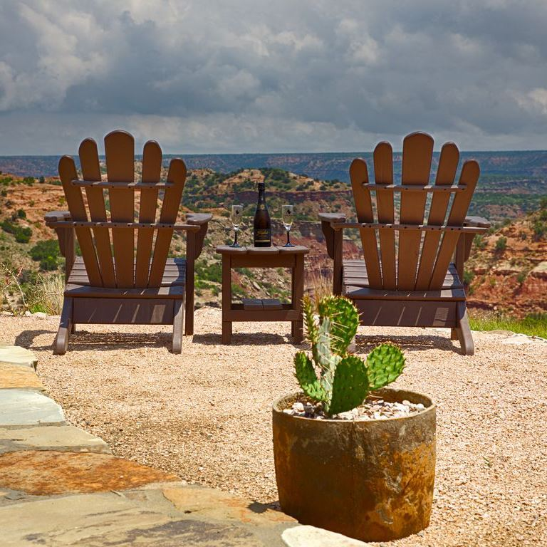 Two wooden lawn chairs over looking Palo Duro Canyon